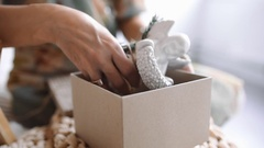 Woman packs gifts for new year, christmas presents for children, plaster figures Stock Footage
