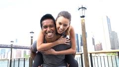 Man giving piggyback ride to girlfriend Stock Footage