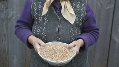 Portrait of very old smiling woman with bowl of wheats' grains in hands 4K Stock Footage