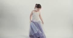 Little girl wearing a purple dress dancing Stock Footage