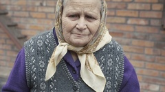 Portrait of very old woman with sadness in eyes smiling to camera in 4K Stock Footage