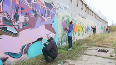 Graffiti artists painting on the wall, exterior Stock Footage