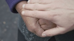 Close up of young hand touches old wrinkled shaking woman's hands in 4K Stock Footage