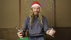 Evil dwarf or bad santa talking on a phone and drinking brandy from a glass Stock Footage