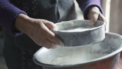 Wrinkled old woman sifting flour in 4K Stock Footage