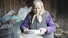 Wrinkled old woman sifting flour in barn in 4K Stock Footage