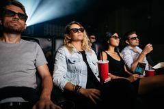 Men and women with drinks watching 3d film Stock Photos
