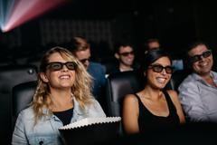 Men and women watching 3d film in theater Stock Photos