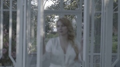 Cute young blonde woman in lingerie open glass doors defocus Flat Stock Footage