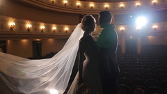 Bride and groom pose stand embrace on stage of empty theater backlit silhouette Stock Footage