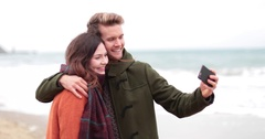 Couple reviewing selfie on beach in Winter Stock Footage