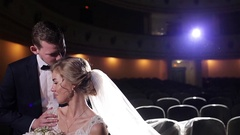 Groom carefully kisses bride forehead calming her down in empty movie theatre Stock Footage