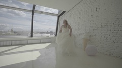 Cute young blonde woman in wedding dress posing for photographer in studio and Stock Footage