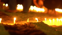 Asian candles on sand in religious ceremony , windy. People light candles. Slow Stock Footage