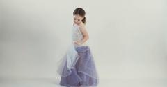 Little girl wearing a purple dress dancing on white studio background Stock Footage