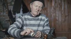 Old wrinkled man hewing his handmade wooden spoon and smiling at camera 4K Stock Footage