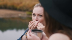 One girl plays harmonica and another girl listens music and drinks hot tea Stock Footage