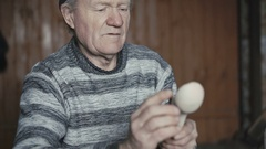 Tired old wrinkled man hewing his handmade wooden spoon and smiling at camera 4K Stock Footage