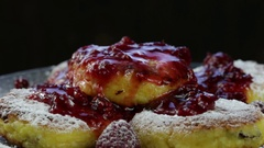 Rotation healthy homemade cheese pancakes with raspberry jam on black background Stock Footage