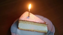 Candle on slice of cake is burning fast until it goes out Stock Footage