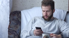 One white young brunette curly-bearded man uses the phone sitting in a chair Stock Footage