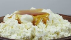Cottage cheese, sour cream and honey in plate. Rotates plate with cottage cheese Stock Footage