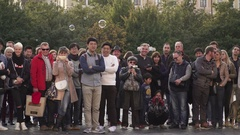 A crowd gathered around a street performer to watch his show Stock Footage