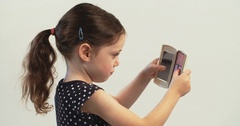 Little girl putting on make up on white background Stock Footage