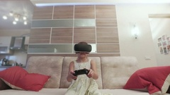 Girl with virtual reality helmet are playing computer console game Stock Footage