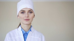 Portrait of a young adult female doctor, looking at camera and smiling Stock Footage