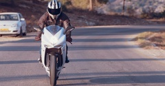 Motorcycle driving on a country road during sunset Stock Footage