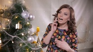 Young cute handsome girl speaks by mobile phone near the Christmas tree Stock Footage
