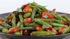 Cooked green beans, red cherry tomato with sesame seeds in plate, close up. Stock Footage