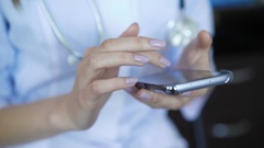 Female therapist using smartphone, sliding, scrolling, zooming on touchscreen Stock Footage