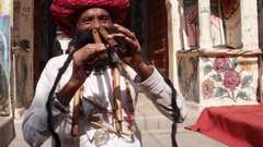 Hand-held male plays the flute with his nose in front of a temple archway, Stock Footage