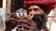Hand-held CU Rajasthani elderly male plays the flute with his nose Stock Footage