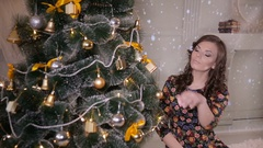 Beautiful girl, young woman decorating Christmas tree, put new year toys and Stock Footage