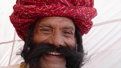 Smiling man salutes with big moustache wearing a red turban and tradition dress Stock Footage