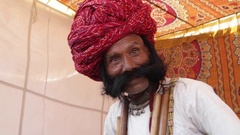 Acting and smiling man with big moustacheand a red turban and tradition dress Stock Footage