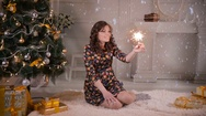 Beautiful girl near christmas tree holding sparkler, bengal fire. Celebrating Stock Footage