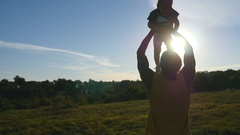 Father playing with his little son outdoor. Dad lifting up his child at nature Arkistovideo