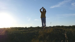 Silhouette of sporty man standing at yoga pose outdoor. Yogi practicing moves Stock Footage
