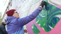 Graffiti artist painting on the wall, exterior Stock Footage