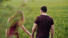 Young couple walking in an oat field. They hold hands, womans hair sway in the Stock Footage
