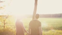 Lovers walk in nature at sunset. Man and woman hug and kiss. Field in the rays Stock Footage