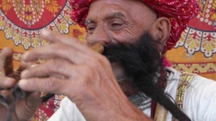 CU Hand-held Rajasthani elderly male starts to play the flute with his nose Stock Footage