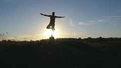 Silhouette of sporty man standing at yoga pose outdoor. Sun as background Stock Footage