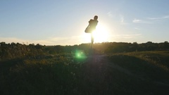 Athlete balancing on one leg. Beautiful sky and sun as background. Stock Footage