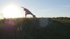 Silhouette of sport man standing at yoga pose outdoor. Sky and sun as background Stock Footage