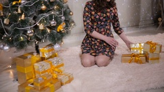 Young attractive woman put gifts under the Christmas tree. Christmas celebration Stock Footage